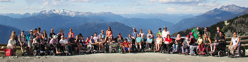 a group of people in wheelchairs smile with able-bodied people against a beautiful BC backdrop.