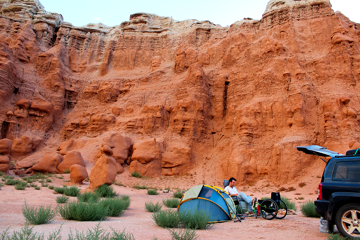 a man in a wheelchair sits next to a tent and his car in the california desert