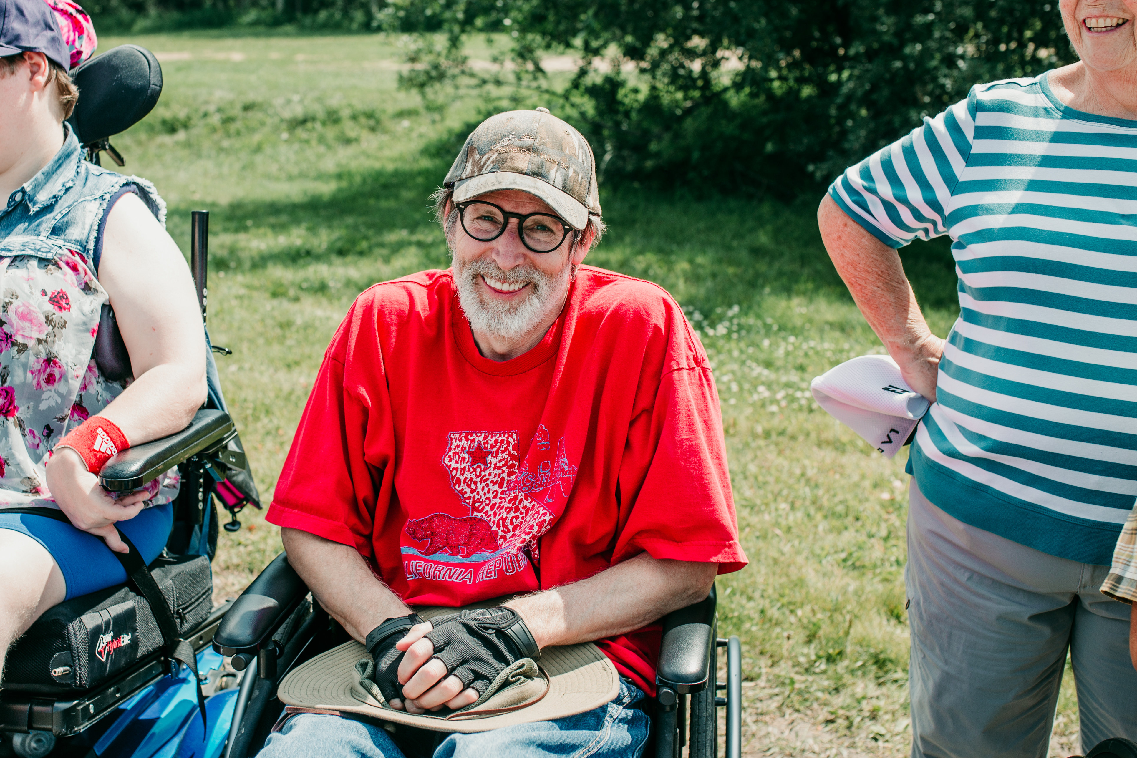 A man in a wheelchair smiles for the camera at a summer barbecue. He is an SCI BC member.