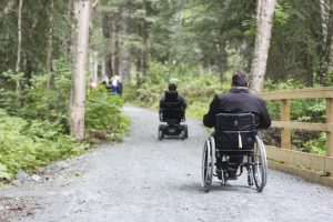 a man in a wheelchair wheels down a trail in the forest
