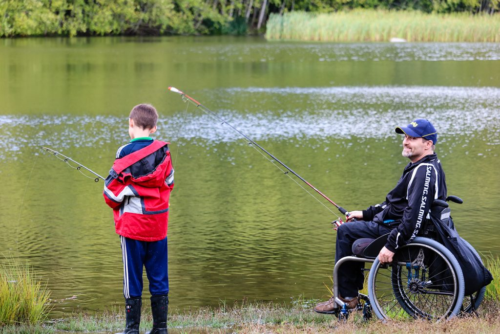 a man in a wheelchair and his son fish side by side at a beautiful lakefront