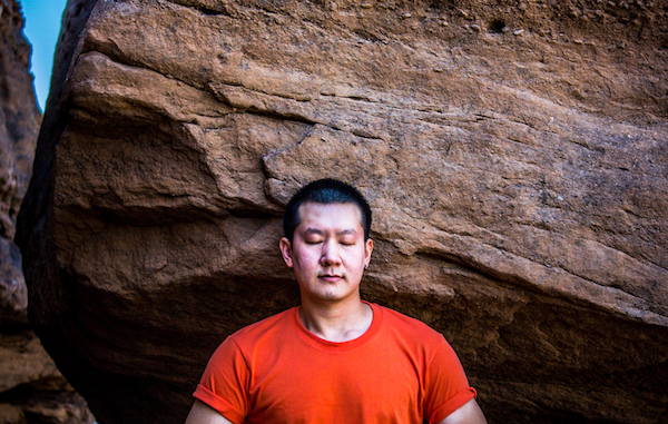 man meditating outdoors near rock wall