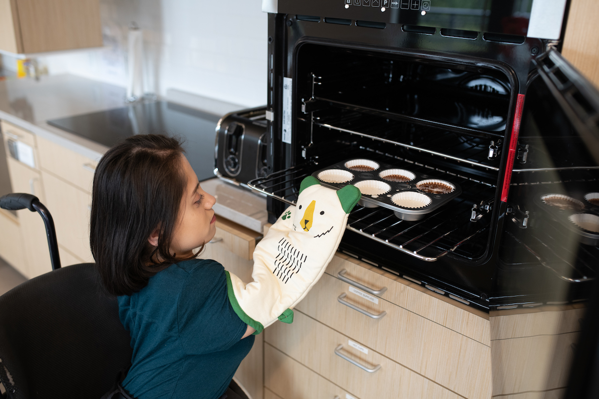 a person in a wheelchair pulls a tray of muffins out of the oven.
