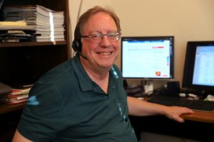 a man sits at a desk with a telephone headset on. He is friendly and smiling for the camera.