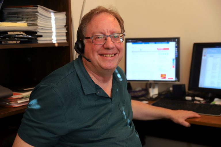 a man sits at a desk with a telephone headset on. He is the staff member for SCI BC's InfoLine.