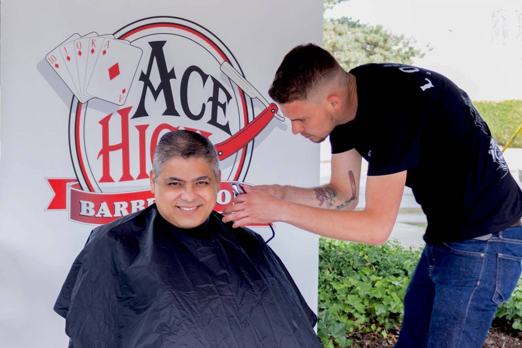a man in a wheelchair gets his haricut by a barber. He is smiling and happy.