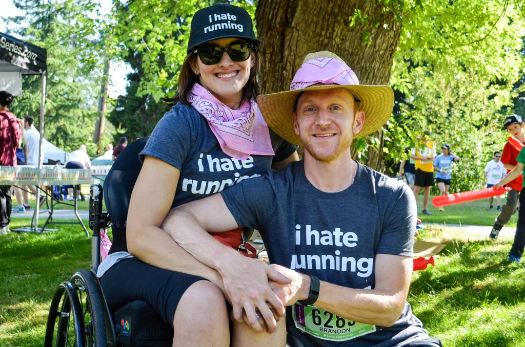 a woman in a wheechair and her husband smile for the camera in matching shirts and racing bibs. They are raising money for spinal cord injury bc.