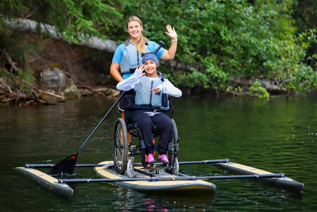 a girl in a wheelchair paddleboards on a beautiful lake with some help from another girl. They smile and wave to the camera.