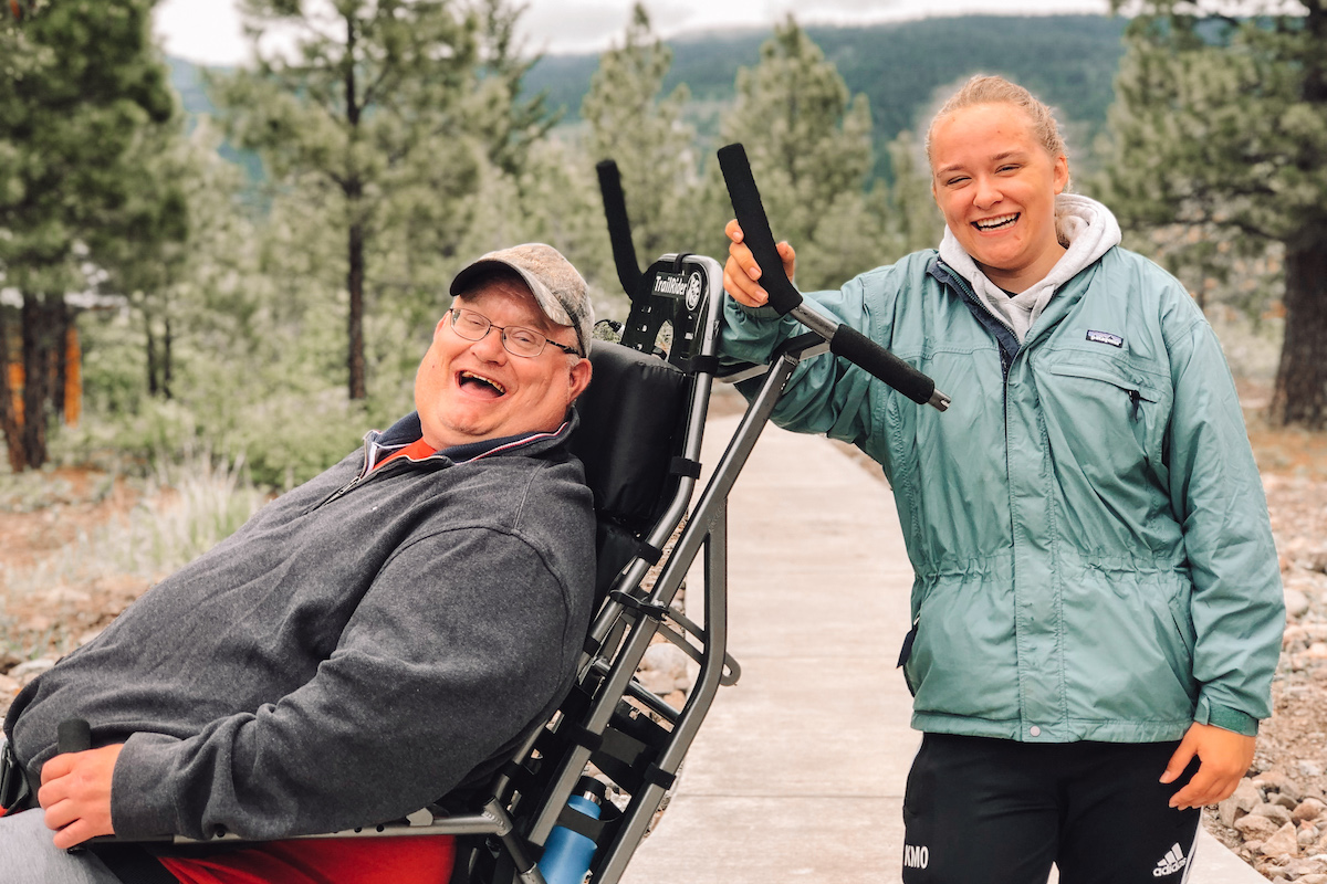 man in wheelchair and woman behind him - both smiling and laughing