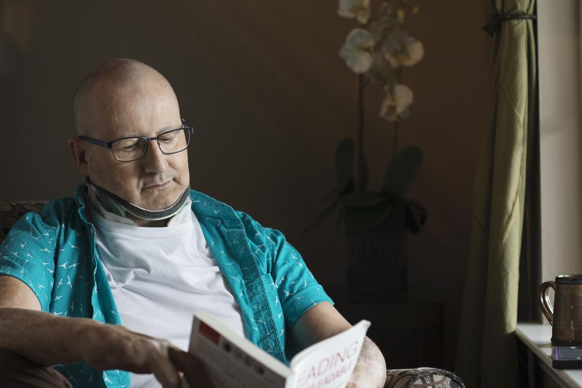 a man in a neck brace reads a book