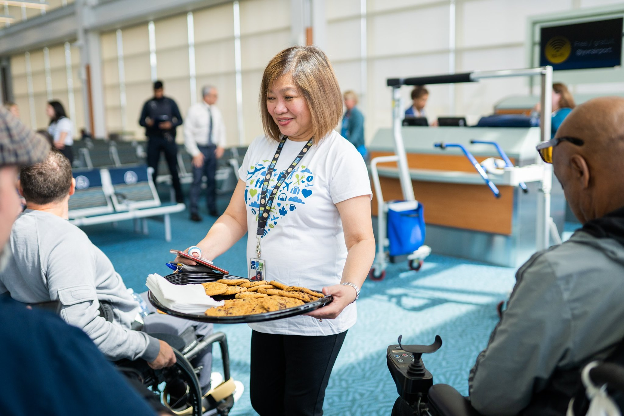 a woman hands out cookies to people in wheelchairs at an event at YVR