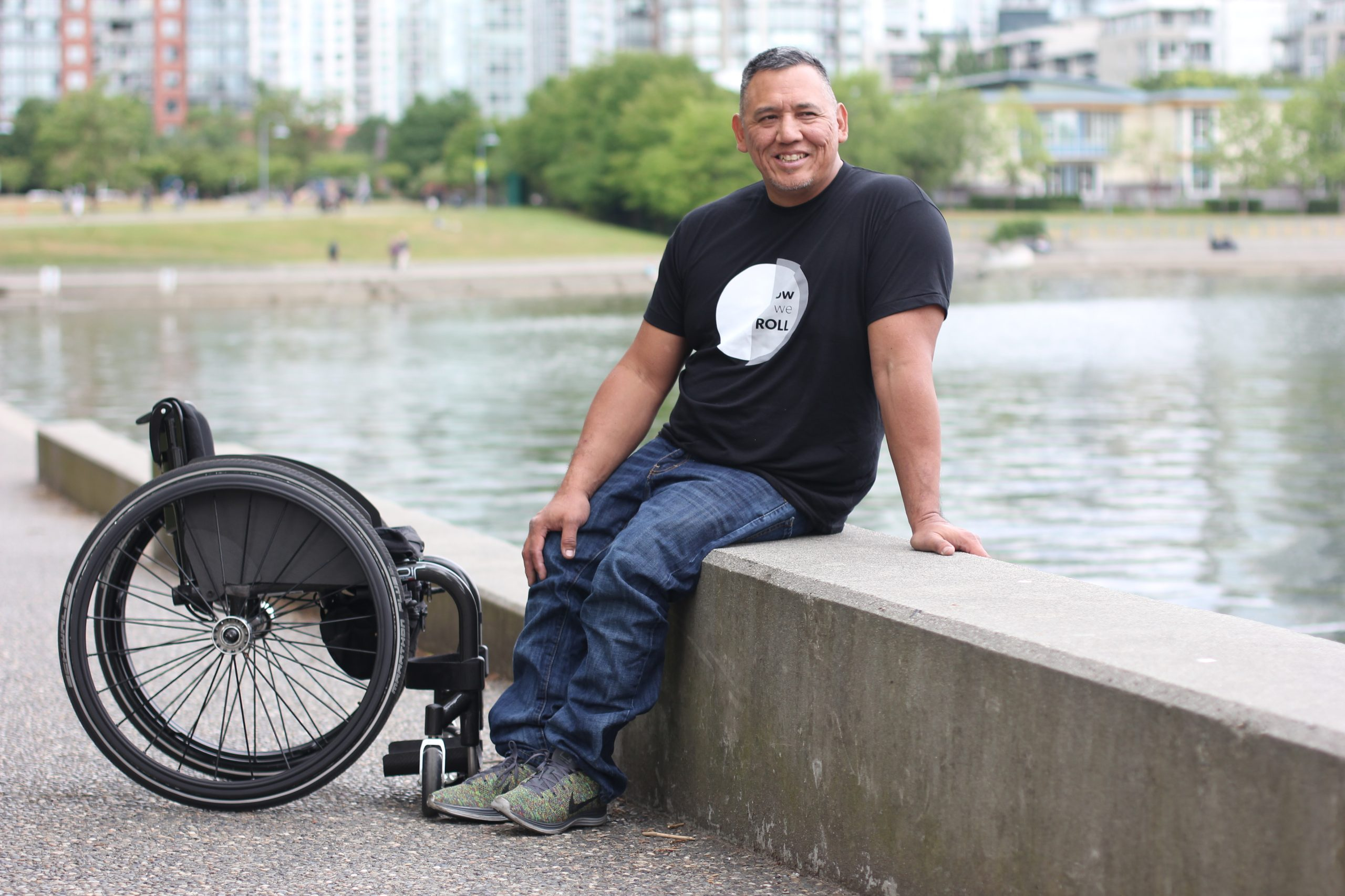 a man poses beside his wheelchair wearing a shirt by a company called Modern Fort and Spinal Cord Injury BC. It says How we Roll.