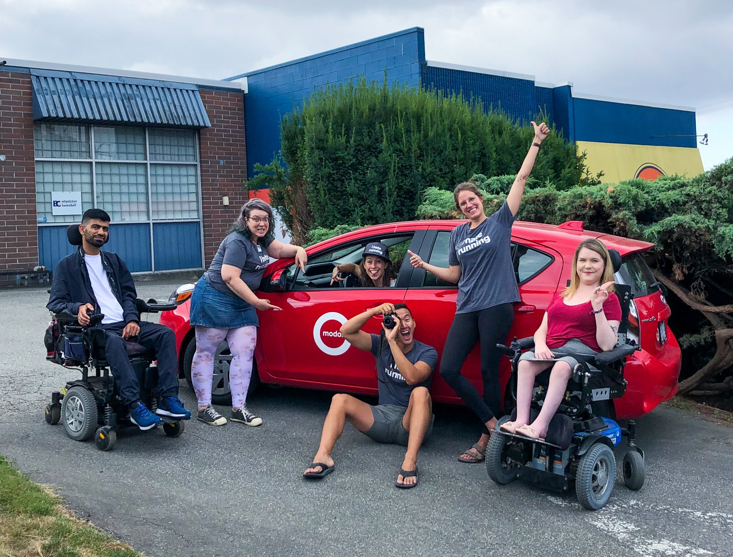 a group photo of people posing in front of a red Modo car. People in the group photo are able bodied and in wheelhcairs.