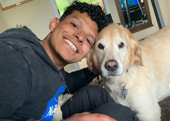 Paulo smiling with a golden lab