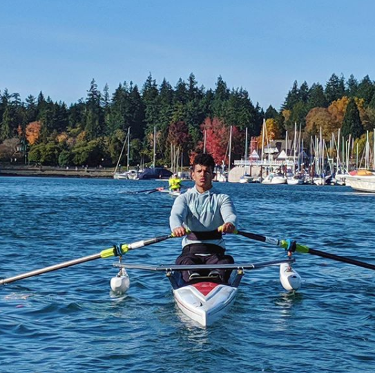 Paulo rowing on blue water with autumn coloured trees and sail boats in the background