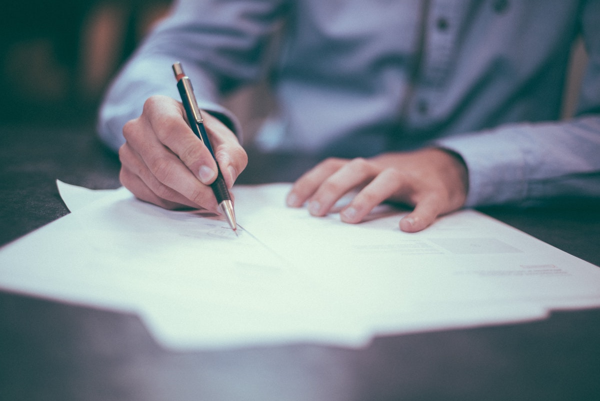 a person signs a stack of papers with a pen