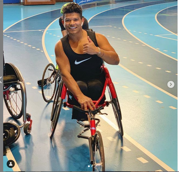 a man on an indoor track gives thumbs up in wheelchair racing chair