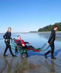 Scott being transferred from water with help from two people pulling and pushing him in a TrailRider along the wet sand