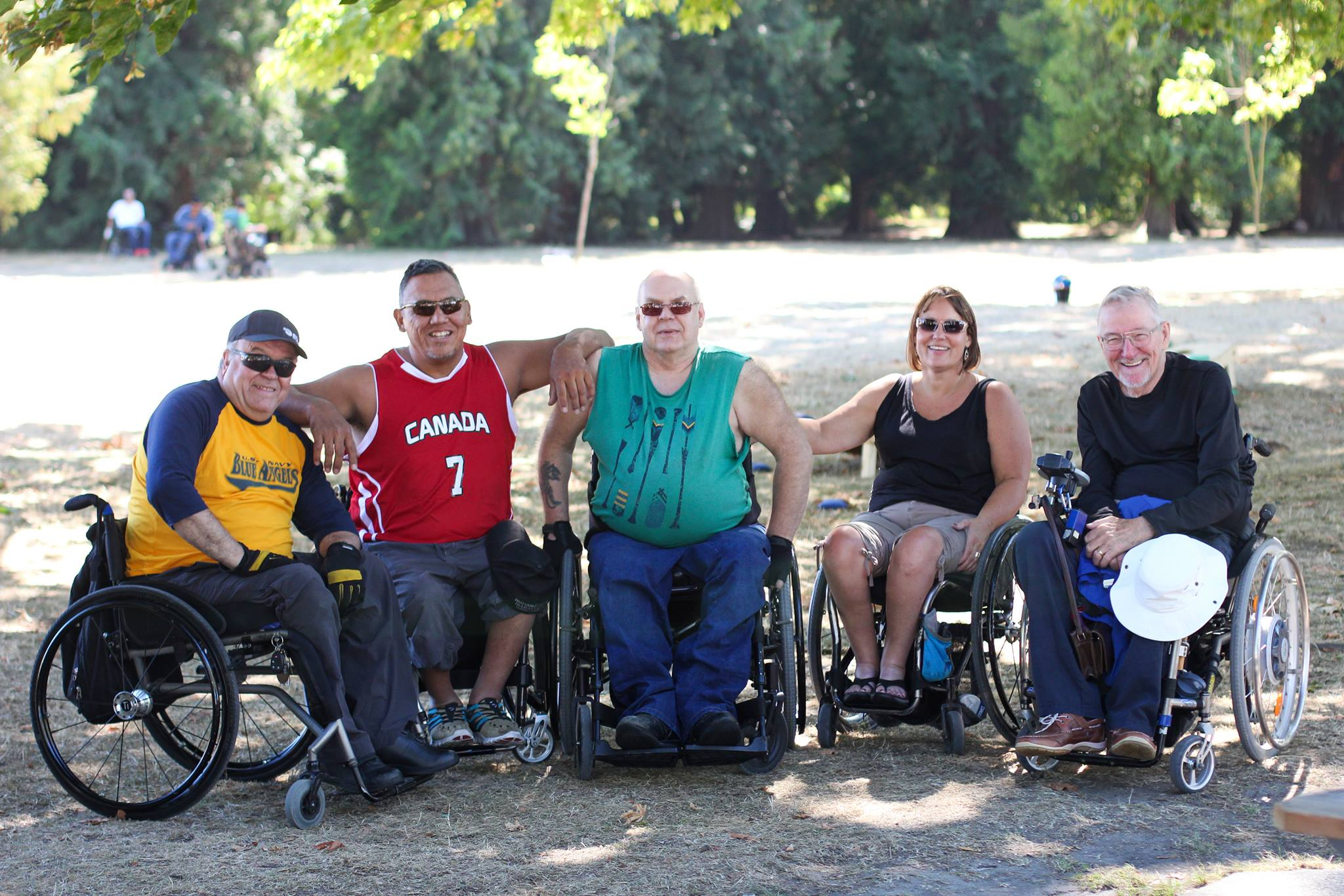 a group of people in wheelchairs of all ages smile for the camera on a summer day