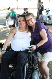 a mom gives her daughter a hug at the park. her daughter is in a wheelchair and smiles for the camera