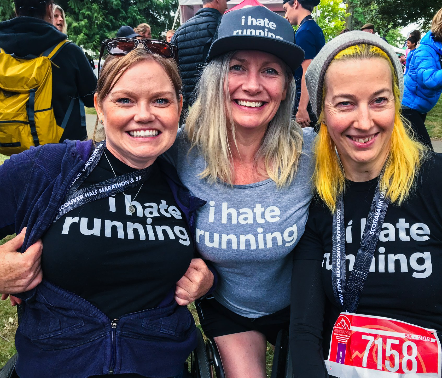 three women smile for the camera at a charity race event. they wear shirts from Spinal Cord Injury BC that say I Hate Running
