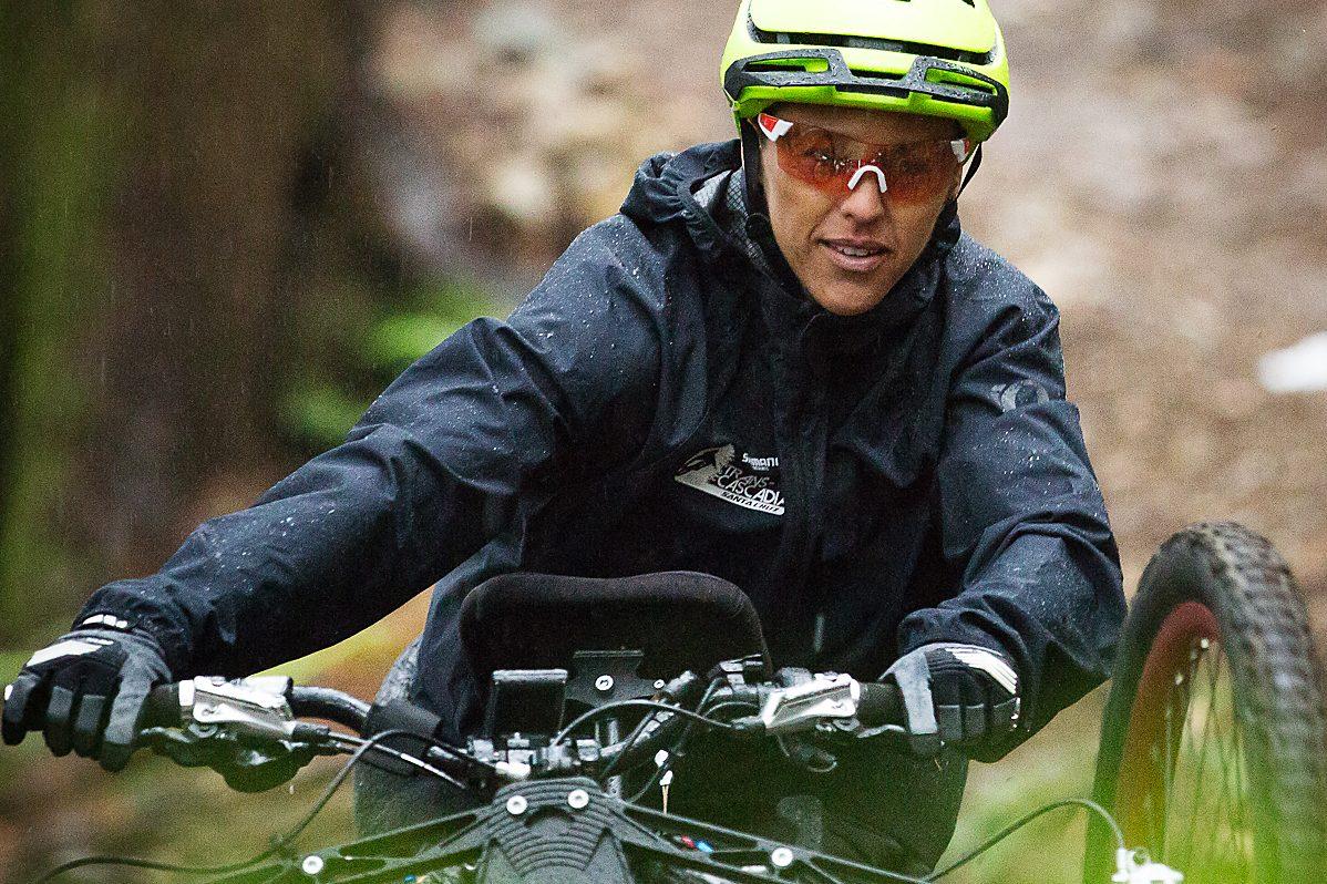 a woman rides an adaptive mountain bike and rips down a rugged mountaion