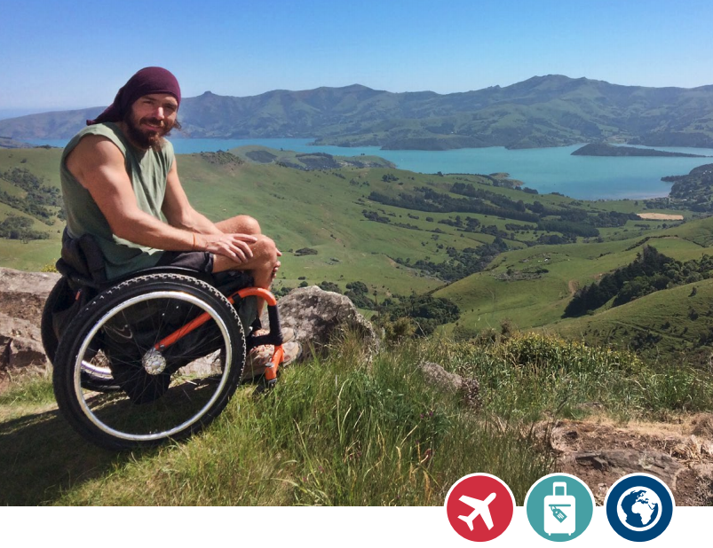 a man in a wheelchair looks out over a beautiful mountain range and lake in an accessible travel spot
