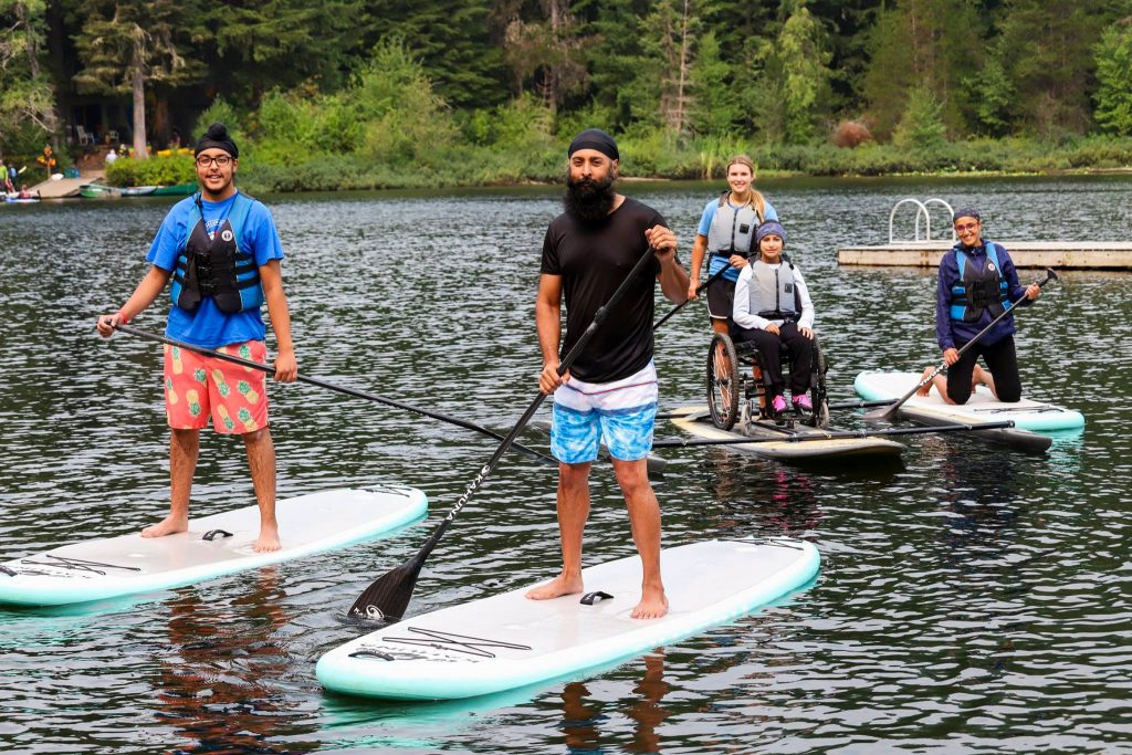 A family of four paddleboards together on a lake. The youngest sibling is in a wheelchair and has some help paddling from a friend