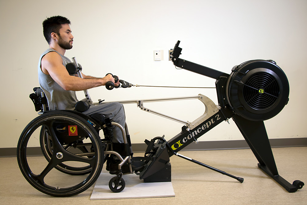 """A man demonstrates the """"A.R.M."""" or Adapted Rowing Machine"""
