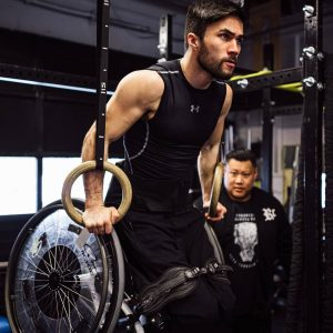 Leo Sammarelli does tricep dips using rings suspended from the ceiling