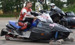 Tyler Tingle sits on his snowmobile racer
