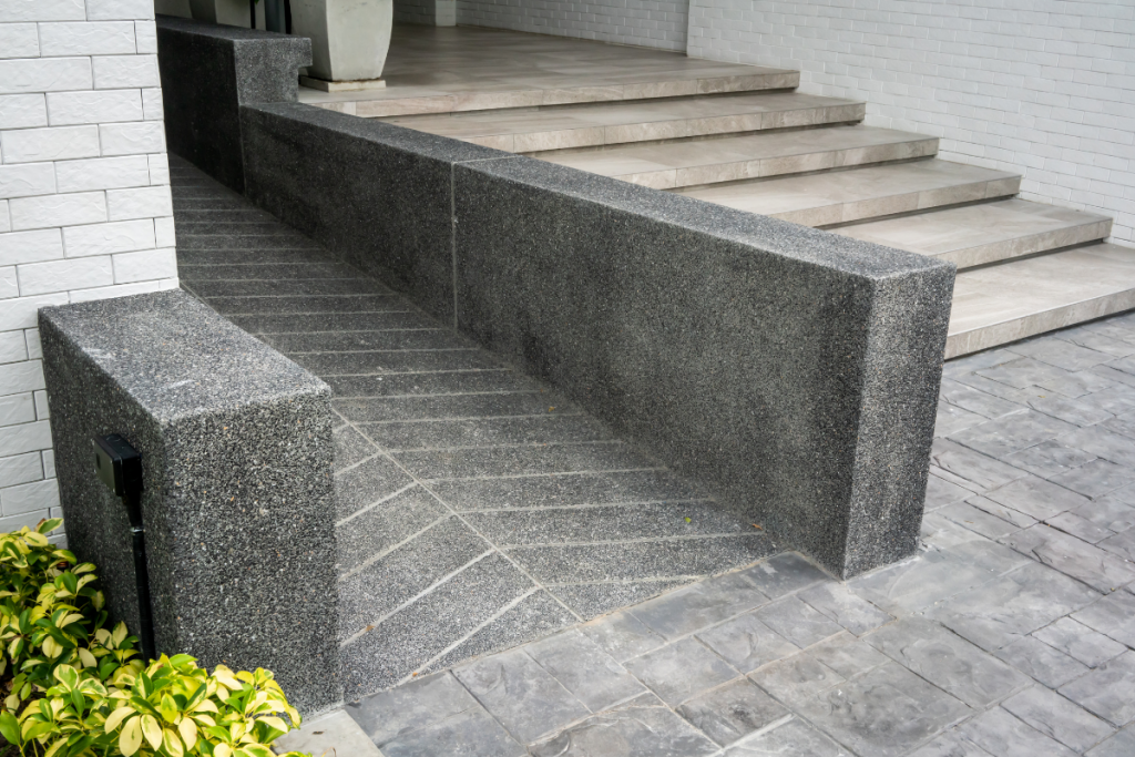 an accessible concrete ramp next to a set of stairs