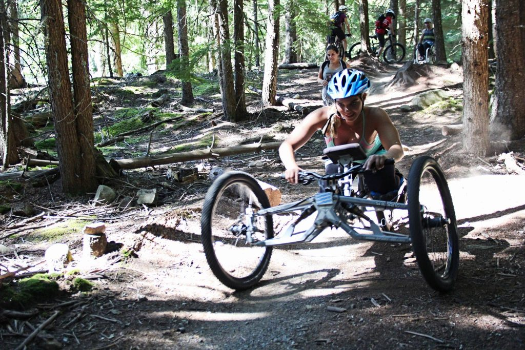 a girl in a handcycle rips down an accessible mountain biking trail