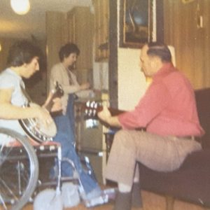 a man in a wheelchair, Pat Harris, plays a banjo. the photo is from the 1970s