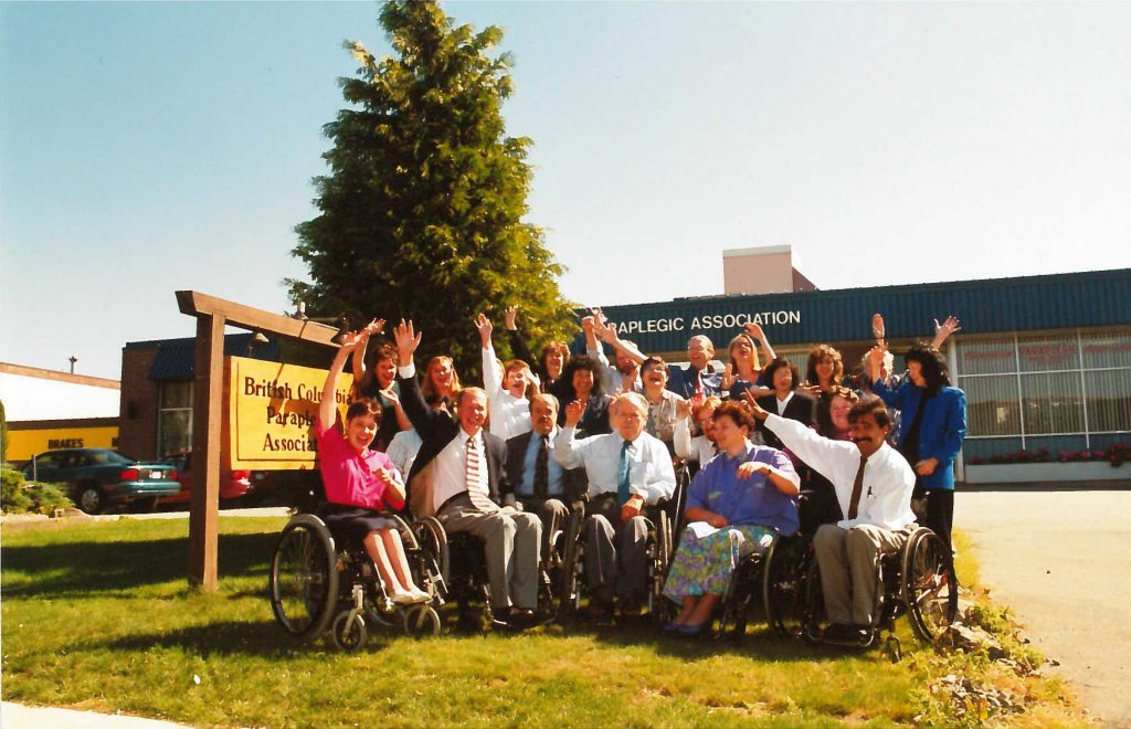 a group of SCI BC staff waving outside of the head office building in Vancouver