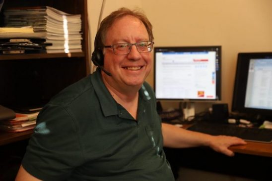 a man with a phone headset on sits at his desk and smiles for the camera. He is a staff member at SCI BC's InfoLine