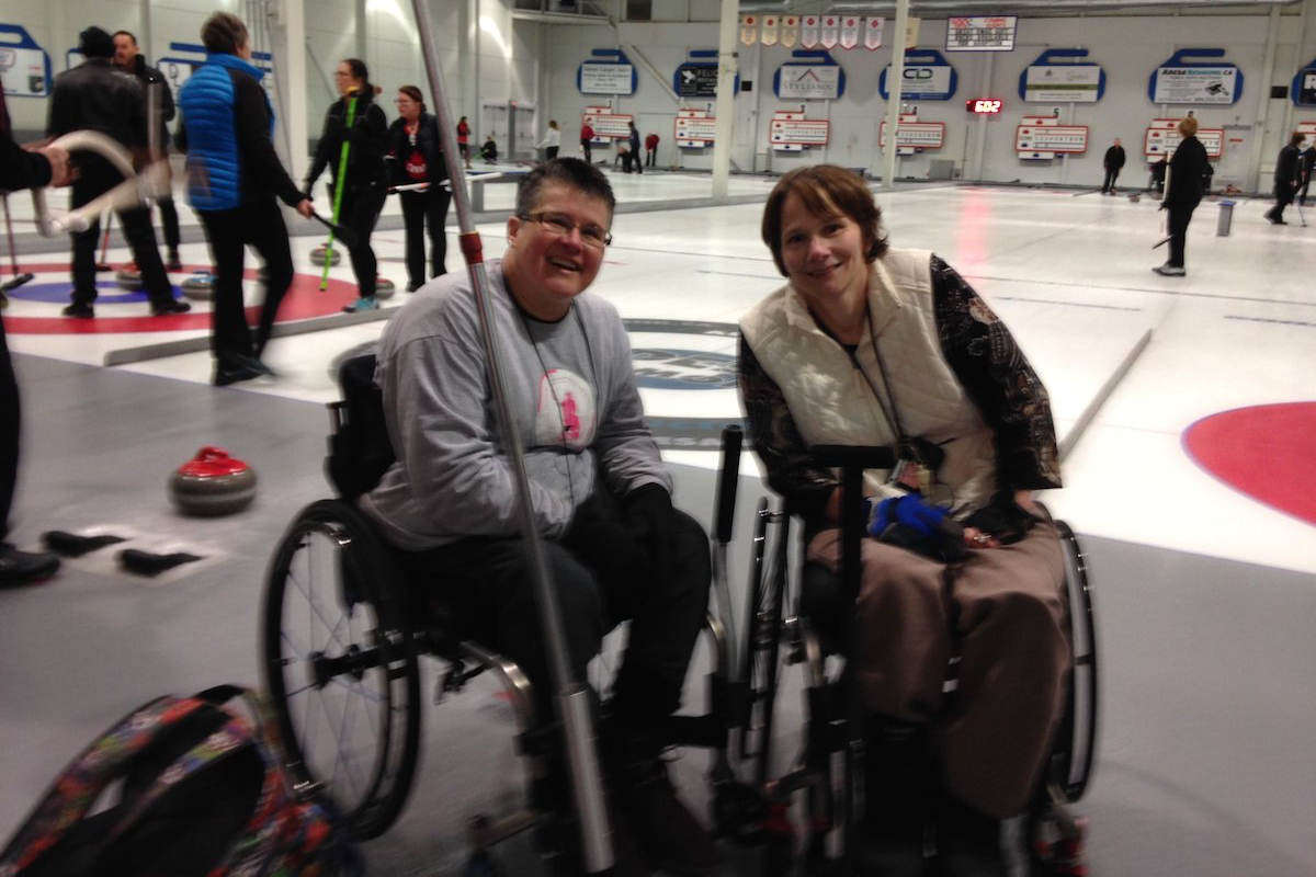 two women in wheelchairs hang out at a curling rink with brooms in their hands, preparing for their next shot.