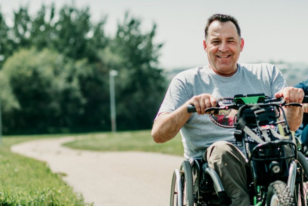 SCI BC peer and donor Pat Harris rides a three wheel power wheelchair on a paved pathway in the summer