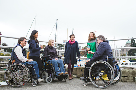 a group of people chat about life and drink coffee at an SCI BC event. Some of them are in wheelchairs or use walking canes for balance.