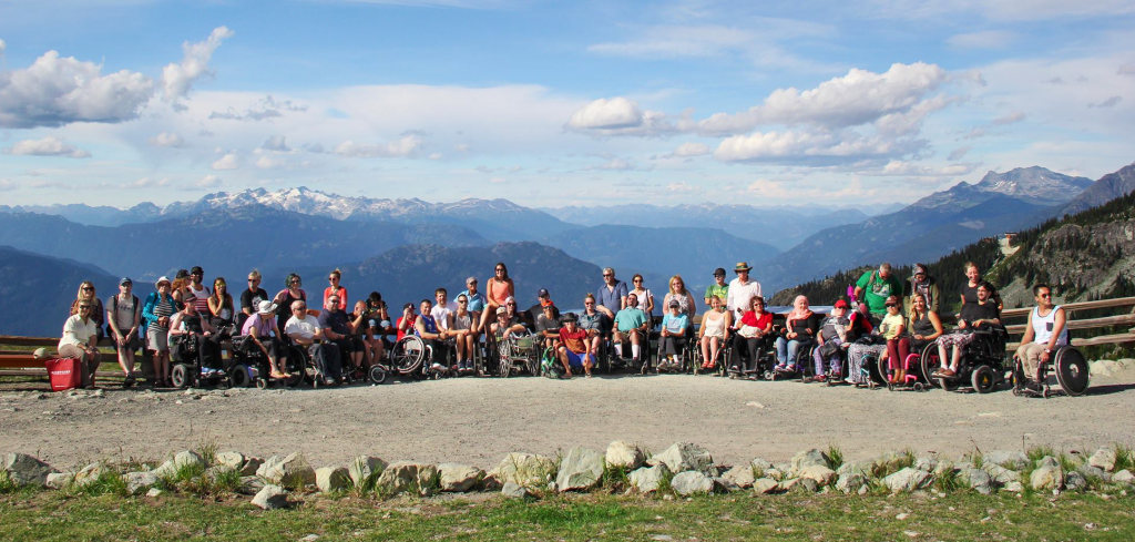 a group of people in wheelchairs with their friends and family on top of a lookout point in Whistler, Canada.