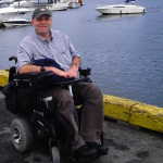 a man in a power wheelchair sits on the deck next to the Pacific Ocean, he smiles for the camera