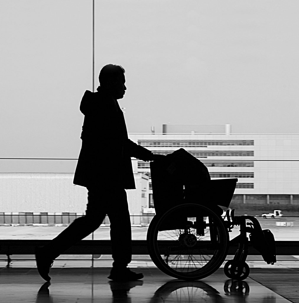 a person with an incomplete SCI pushes their wheelchair through an airport terminal