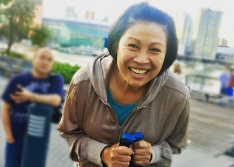 a women with walking stick aids smiles for the camera on a boardwalk in Vancouver