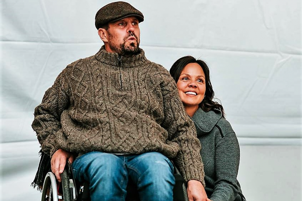 a man in a wheelchair and his wife smiling together at a big event