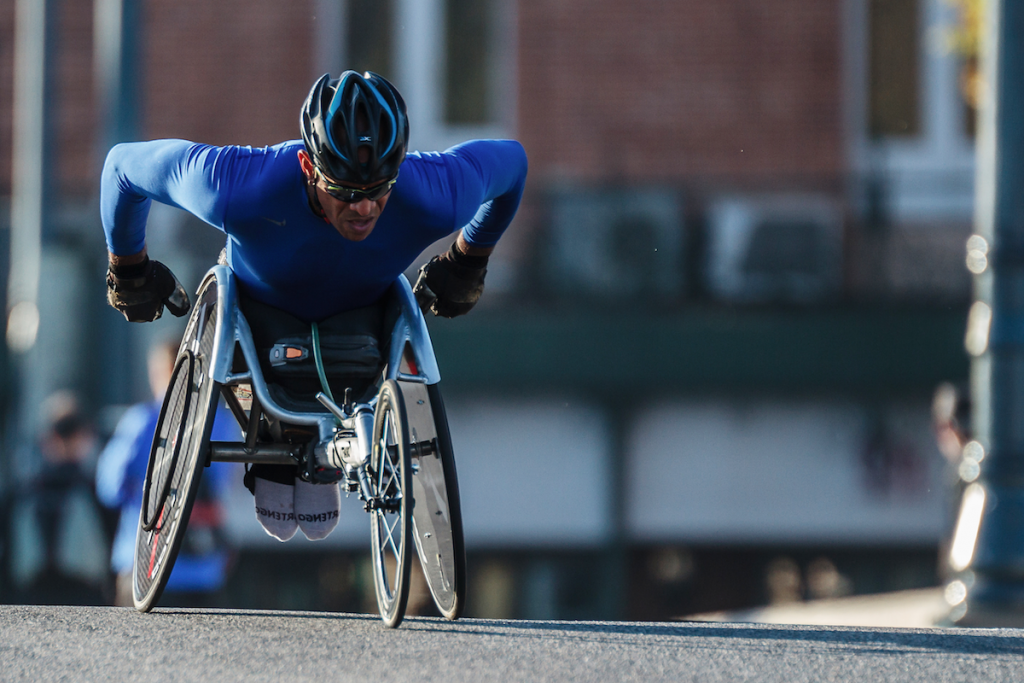 an athletic man in a sports wheelchair handcycles down a street
