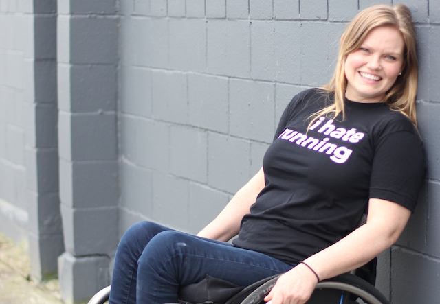A young woman in a wheelchair leaning back and smiling