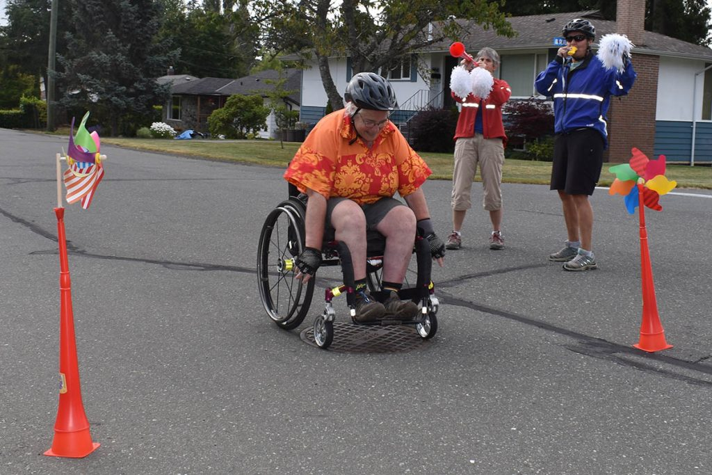 a women in a wheelchair crosses the finish line of the scotiabank charity challenge