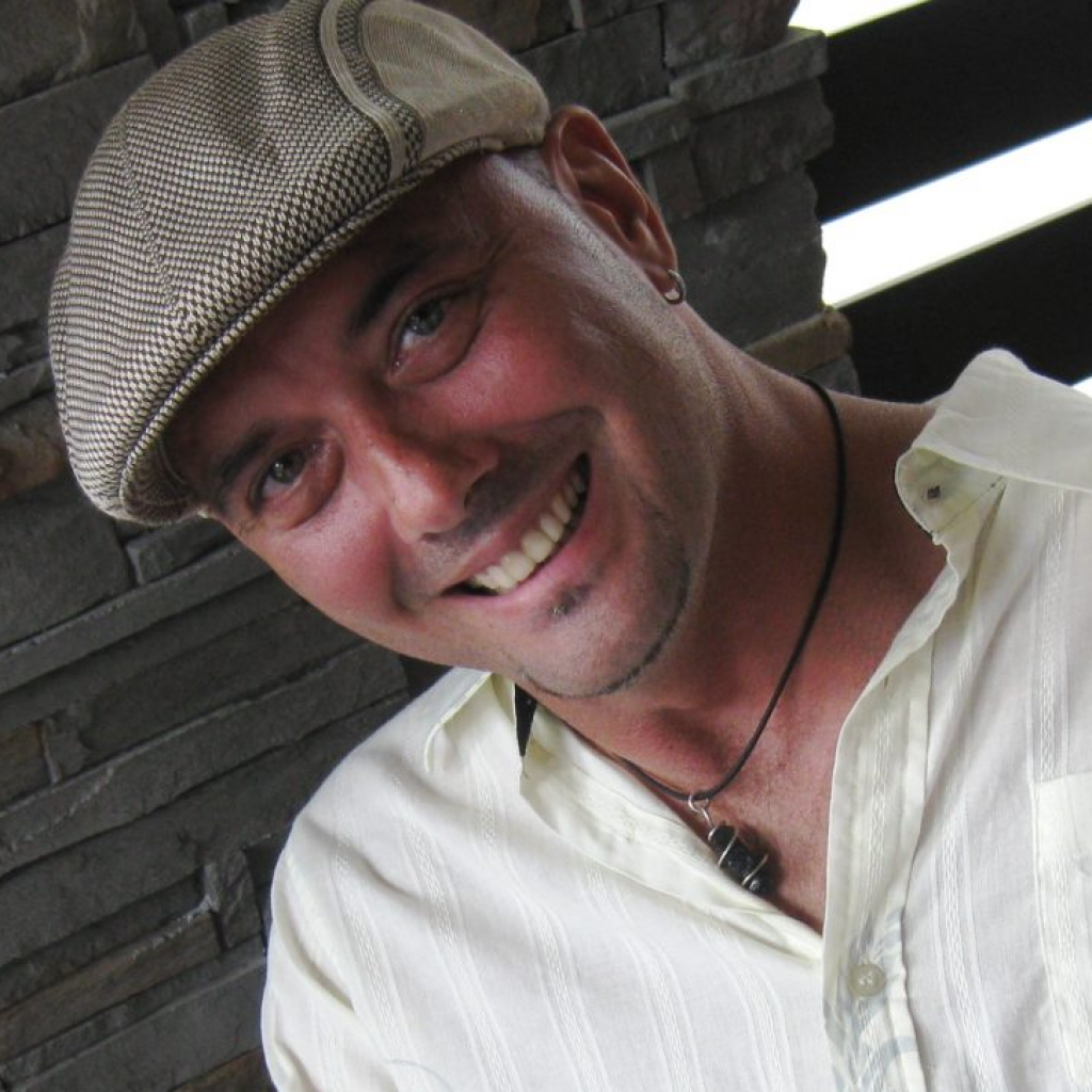 photo of brad jacobsen wearing a hat and a white shirt with a pendant necklace, smiling for the camera