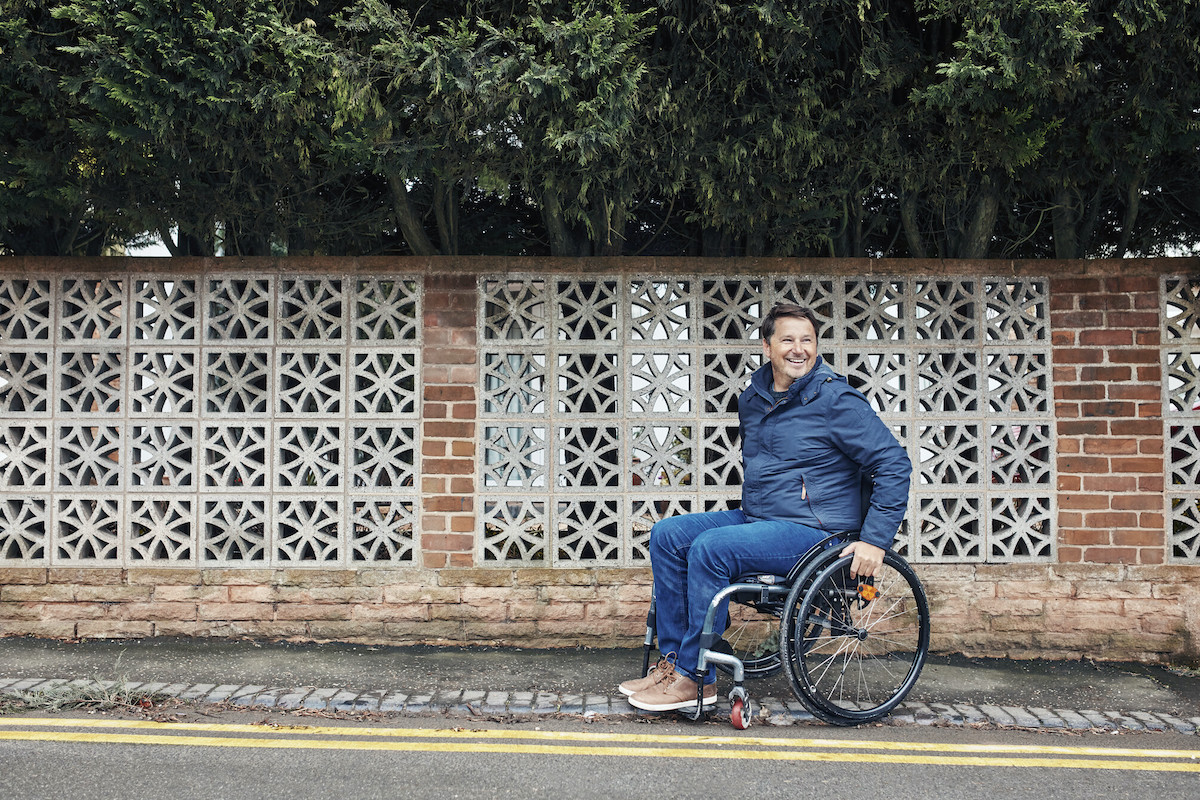 a man in a wheelchair wheeling on a sidewalk and smiling