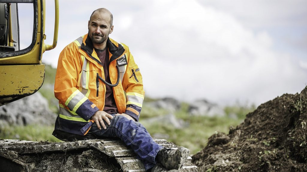 a close up of Shance Bunce, sitting on the tracks of his excavator in a yellow hazard vest and blue jeans